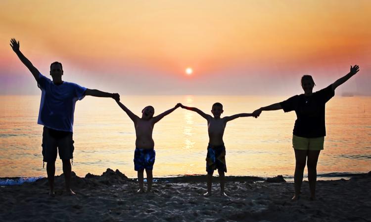Familie vor Sonnenuntergang am Meer